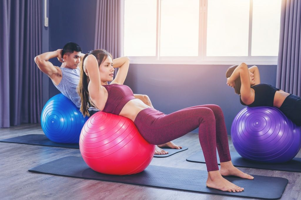 group-fit-people-working-out-pilates-class-with-fitness-ball.jpg